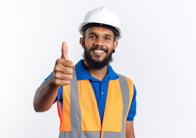 Smiling young afro-american builder man in uniform with safety helmet thumbing up isolated on white background with copy space