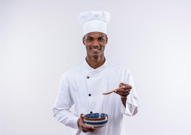 シェフの制服を着た笑顔の若いアフリカ系アメリカ人料理人は、コピースペースと孤立した白い背景の上のボウルを保持し、ポイントします