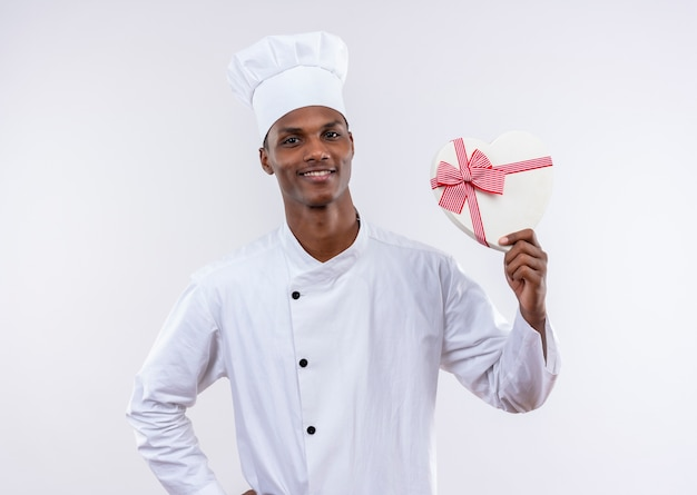 シェフの制服を着て笑顔の若いアフリカ系アメリカ人料理人は、コピースペースと白い背景で隔離のハート型のボックスを保持します。