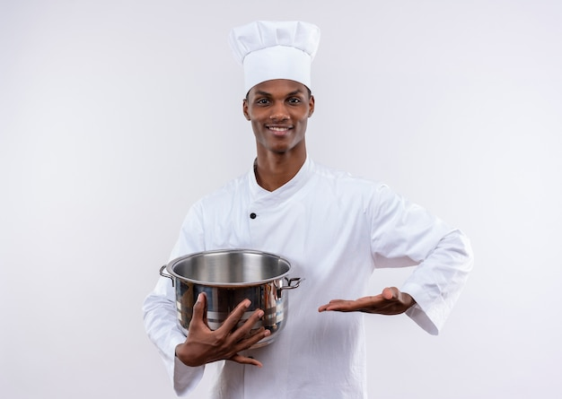 シェフの制服を着た笑顔の若いアフリカ系アメリカ人料理人は鍋を保持し、コピースペースで孤立した白い背景に手をまっすぐに保ちます