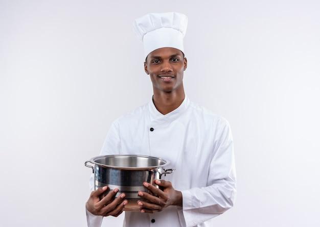 シェフの制服を着た笑顔の若いアフリカ系アメリカ人料理人は鍋を保持し、コピースペースで孤立した白い背景の上のカメラを見てください