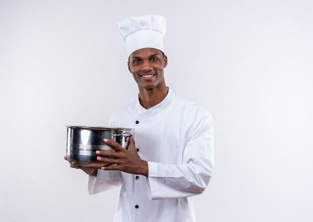 シェフの制服を着た笑顔の若いアフリカ系アメリカ人料理人は、コピースペースと孤立した白い背景に両手で鍋を保持します。