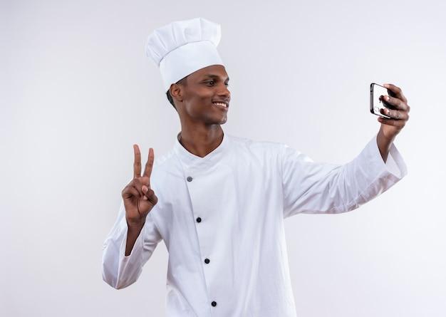 シェフの制服を着た若いアフリカ系アメリカ人料理人の笑顔は、コピースペースと孤立した白い背景の上の電話とジェスチャーの勝利のサインを見てください