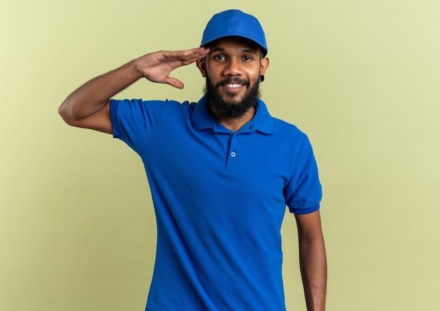 Sorridente giovane fattorino afro-americano che fa il saluto militare isolato su sfondo verde oliva con spazio di copia