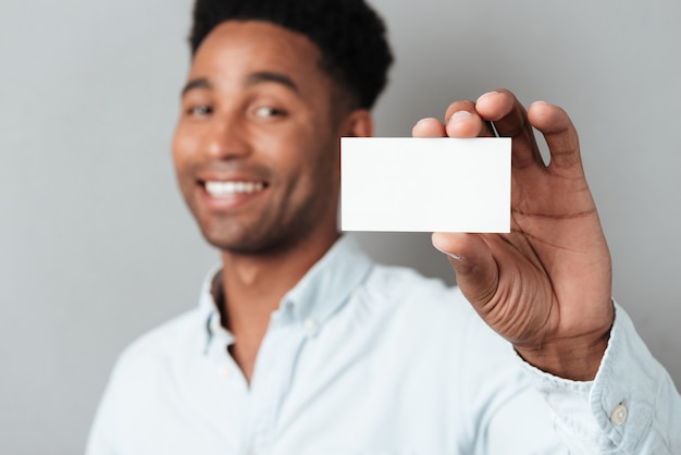 Smiling young afro american guy showing blank business card
