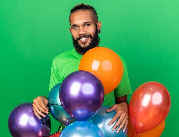 Sorridente giovane ragazzo afroamericano che indossa una maglietta verde in piedi dietro i palloncini