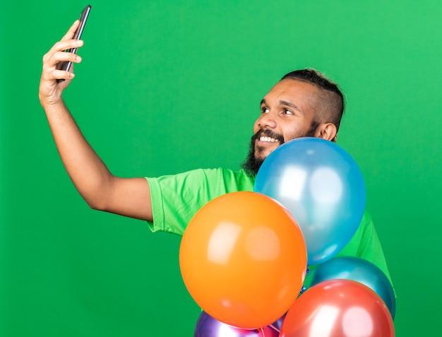 풍선 뒤에 서 있는 녹색 티셔츠를 입은 웃고 있는 젊은 아프리카계 미국인 남자가 셀카를 찍는다