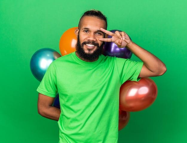 Sorridente giovane ragazzo afroamericano che indossa una maglietta verde in piedi davanti al gesto di pace dei palloncini