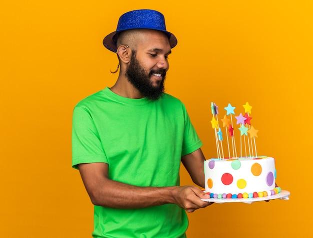 パーティーハットをかぶってケーキを見て笑顔の若いアフリカ系アメリカ人の男