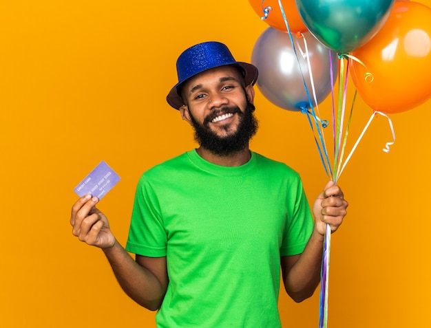 Smiling young afro-american guy wearing party hat holding balloons and credit card