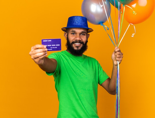 Smiling young afro-american guy wearing party hat holding balloons and holding out credit card at camera