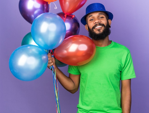 Smiling young afro-american guy wearing party hat holding balloons isolated on blue wall