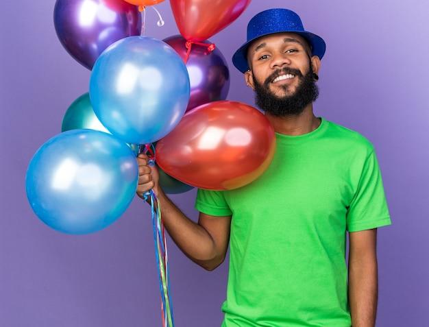 青い壁に分離された風船を保持しているパーティーハットを身に着けている若いアフリカ系アメリカ人の男を笑顔