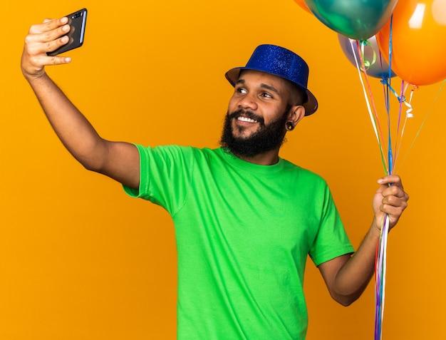 Il giovane ragazzo afroamericano sorridente che indossa un cappello da festa tiene in mano palloncini e si fa un selfie