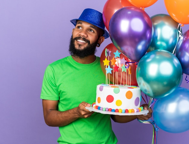 Smiling young afro-american guy wearing party hat holding balloons with cake isolated on blue wall with copy space
