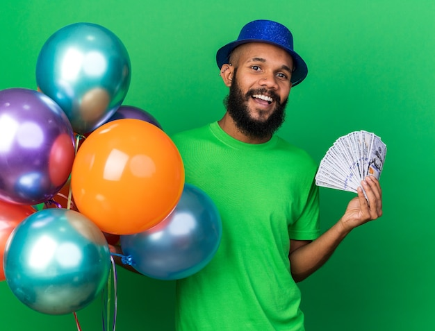 Smiling young afro-american guy wearing party hat holding balloons with cash isolated on green wall