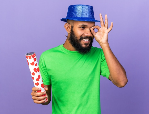 Smiling young afro-american guy wearing party hat holding confetti cannon showing look gesture