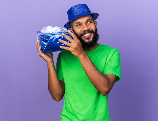顔の周りにギフトボックスを保持しているパーティーハットを身に着けている若いアフリカ系アメリカ人の男を笑顔