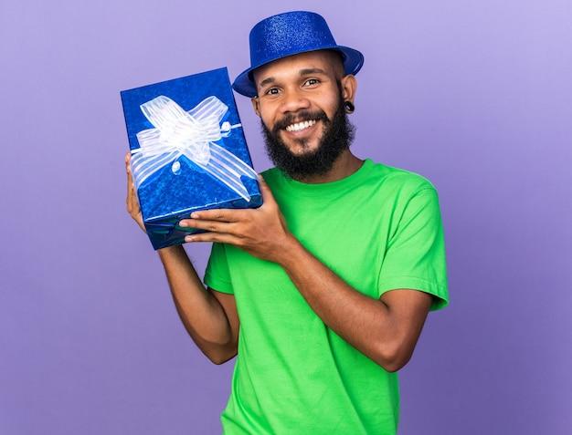 Sorridente giovane ragazzo afroamericano che indossa un cappello da festa che tiene in mano una scatola regalo isolata sulla parete blu