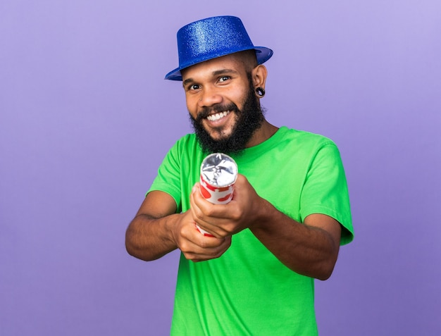Smiling young afro-american guy wearing party hat holding out confetti cannon at front isolated on blue wall