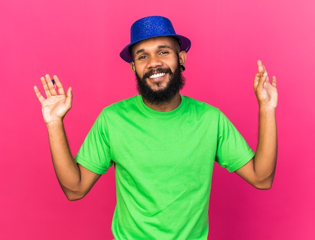 Smiling young afro-american guy wearing party hat holding party whistle showing okay gesture isolated on pink wall