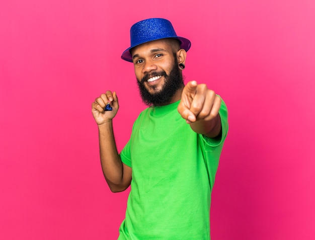 Smiling young afro-american guy wearing party hat holding party whistle showing you gesture