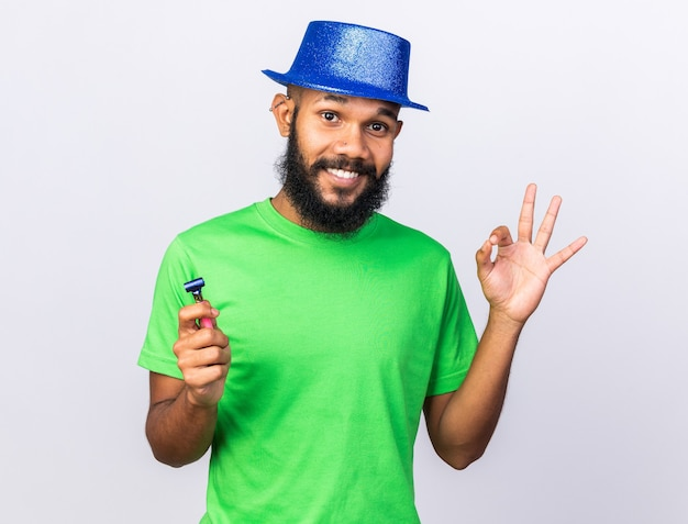 Smiling young afro-american guy wearing party hat showing okay gesture holding party whistle