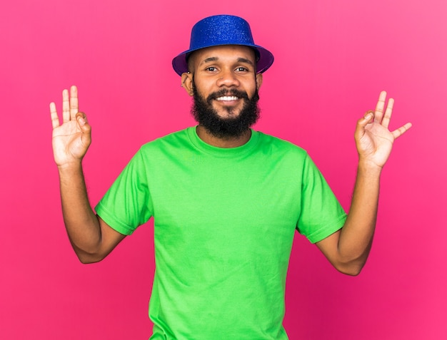 Smiling young afro-american guy wearing party hat showing okay gesture isolated on pink wall