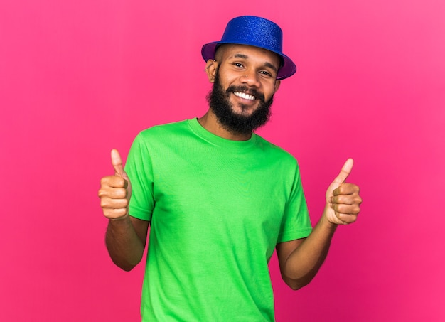 Smiling young afro-american guy wearing party hat showing thumbs up isolated on pink wall