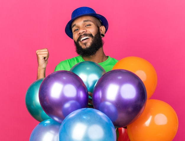 Smiling young afro-american guy wearing party hat standing behind balloons showing yes gesture isolated on pink wall
