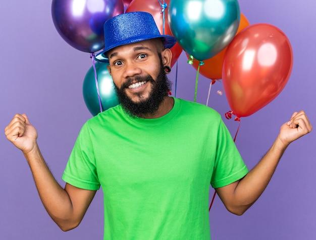 Sorridente giovane ragazzo afroamericano che indossa un cappello da festa in piedi davanti a palloncini che allargano le mani