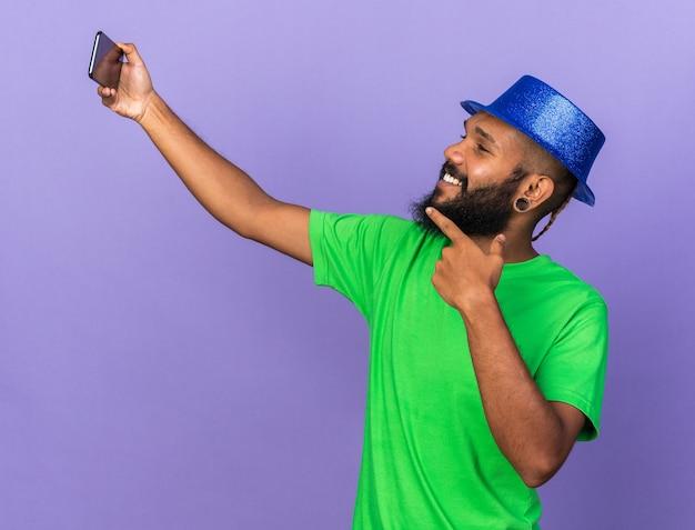파티 모자를 쓰고 웃고 있는 젊은 아프리카계 미국인 남자가 전화에서 셀카 포인트를 찍습니다