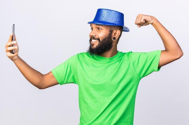 파티 모자를 쓰고 웃고 있는 젊은 아프리카계 미국인 남자는 강한 몸짓을 보여주는 셀카를 찍습니다