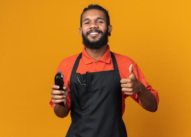 親指を上に見せてバリカンを保持している制服を着ている若いアフリカ系アメリカ人の男性理髪師の笑顔