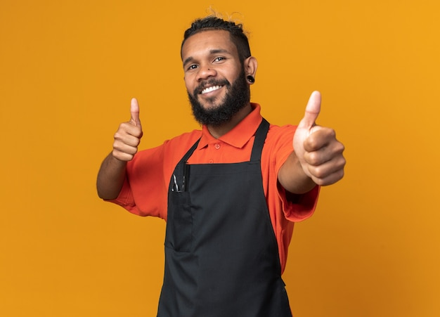 Smiling young afro-american male barber wearing uniform showing thumbs up