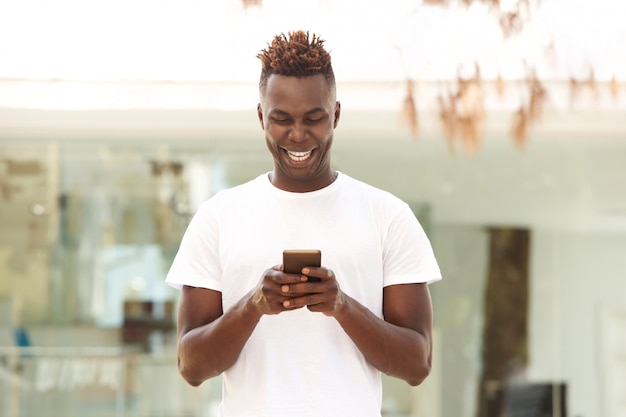Smiling young afro american man using mobile phone standing outdoors in city