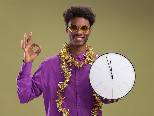 Улыбающийся молодой афро-американский мужчина в очках с гирляндой из мишуры на шее держит часы, глядя в камеру, делает хорошо, знак изолирован на оливково-зеленом фоне