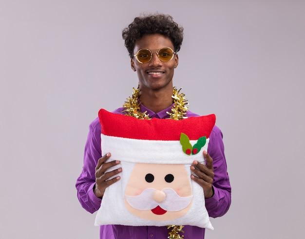 白い背景で隔離のカメラを見てサンタクロースの枕を保持している首の周りに見掛け倒しの花輪と眼鏡をかけて笑顔の若いアフリカ系アメリカ人の男