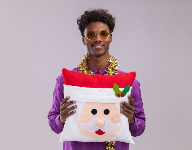 Smiling young afro-american man wearing glasses with tinsel garland around neck holding santa claus pillow looking at camera isolated on white background