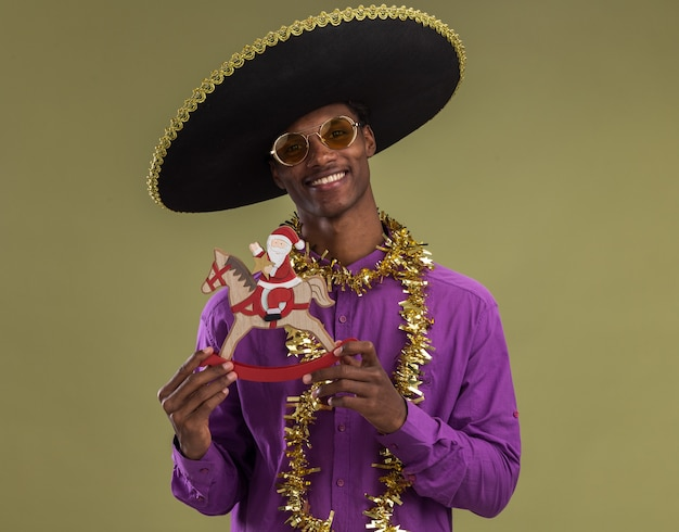 Smiling young afro-american man wearing mexican hat and glasses with tinsel garland around neck holding santa on rocking horse figurine looking at camera isolated on olive green background