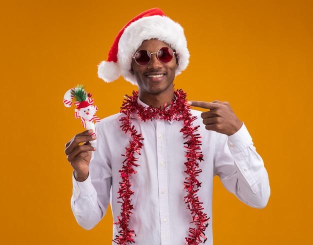 オレンジ色の背景に分離されたカメラを見てキャンディケインの飾りを保持し、指している首の周りに見掛け倒しの花輪とサンタの帽子とメガネを身に着けている若いアフリカ系アメリカ人男性の笑顔