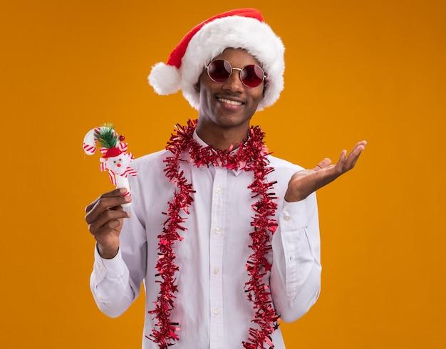 オレンジ色の背景に分離された空の手を示すカメラを見てキャンディケインの飾りを保持している首の周りに見掛け倒しの花輪とサンタの帽子とメガネを身に着けている若いアフリカ系アメリカ人男性の笑顔