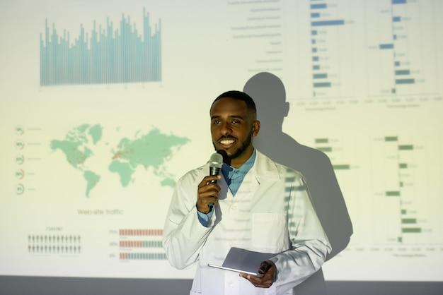 白衣を着た若いアフリカ系アメリカ人の医学者が投影スクリーンに立ち向かい、大会でコロナウイルス薬を提供している笑顔