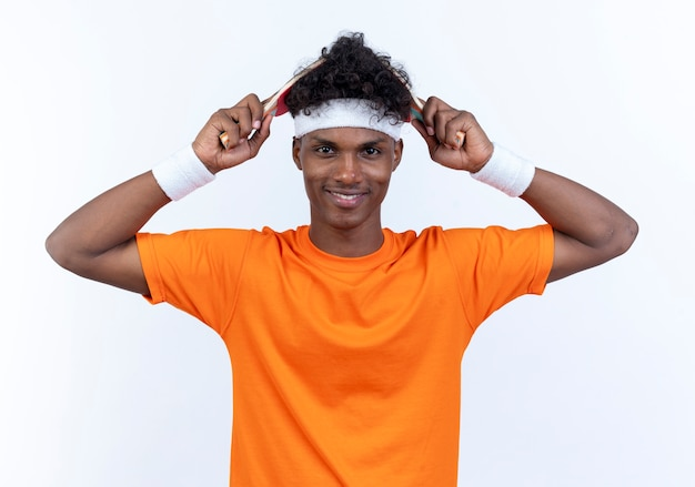 머리띠와 팔찌를 입고 웃는 젊은 아프리카 계 미국 흑인 스포티 한 남자가 흰 벽에 고립 된 탁구 라켓으로 머리를 덮었습니다.
