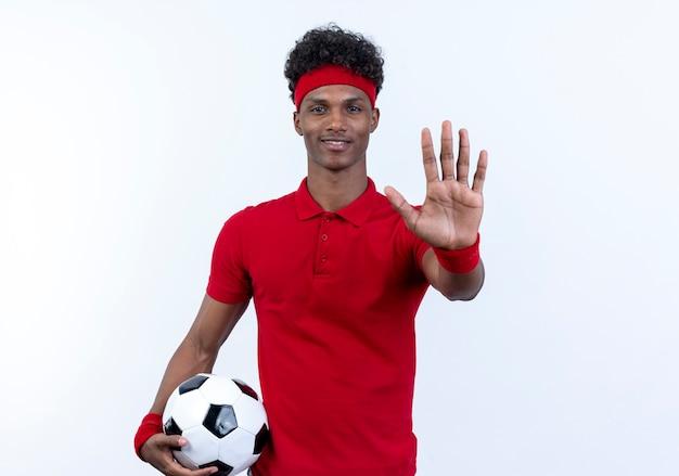 白で隔離の停止ジェスチャーを示すボールを保持しているヘッドバンドとリストバンドを身に着けている若いアフリカ系アメリカ人のスポーティな男の笑顔