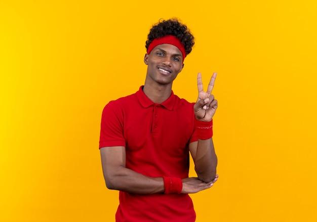 黄色の背景に分離された平和のジェスチャーを示すヘッドバンドとリストバンドを身に着けている若いアフリカ系アメリカ人のスポーティな男の笑顔