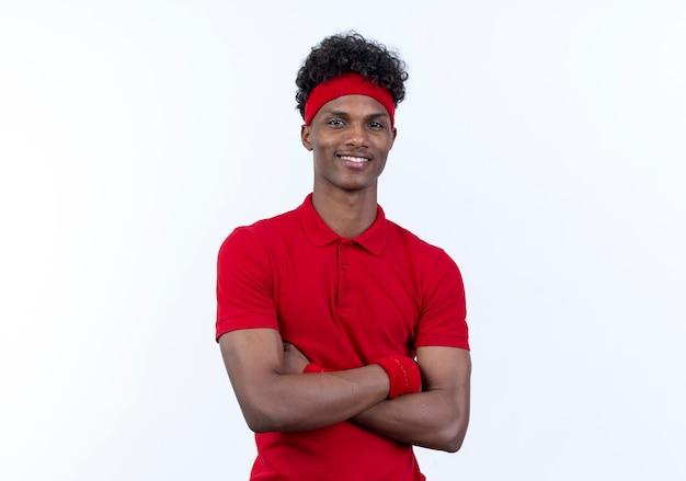 Sorridente giovane afro-americano sportivo uomo indossa la fascia e il braccialetto che attraversano le mani isolate su bianco