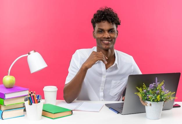Sorridente giovane studente afroamericano seduto alla scrivania con gli strumenti della scuola che sembra isolato sul muro rosa