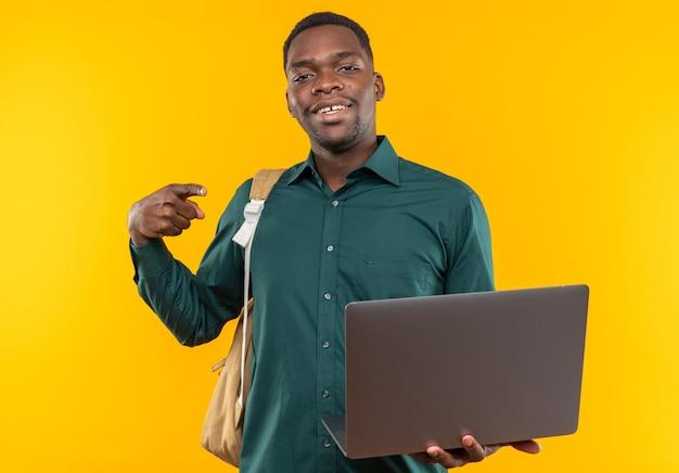 Улыбающийся молодой афро-американский студент с рюкзаком, держащий и указывающий на ноутбук