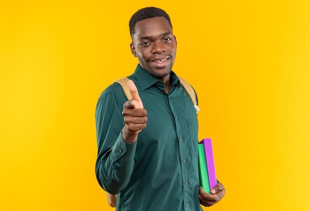 Sorridente giovane studente afroamericano con zaino in mano libri e puntato davanti